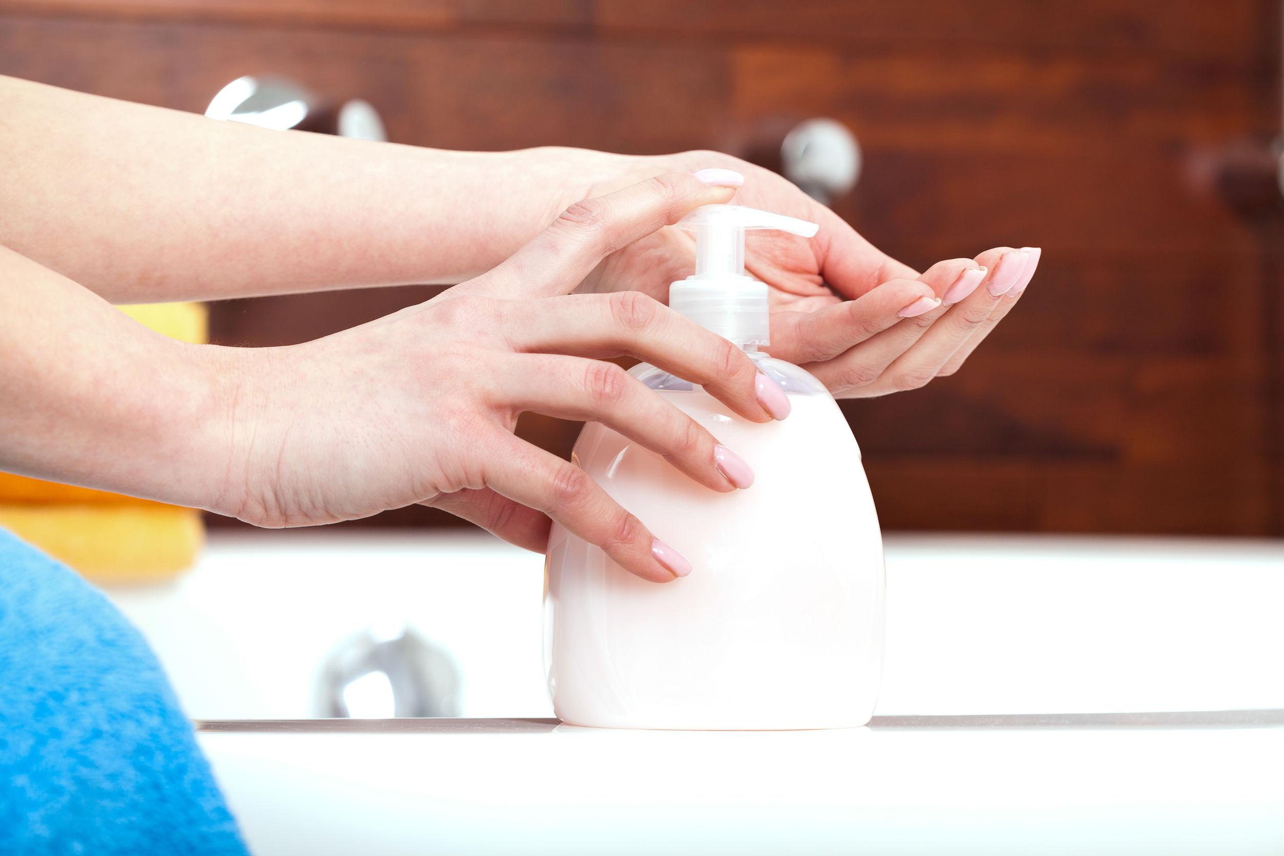 Eine Frau wäscht sich gerade am Waschbecken mit einem Seifenspender die Hände.