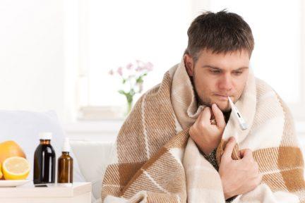 Kerkälteter Mann mit Thermometer im Mund