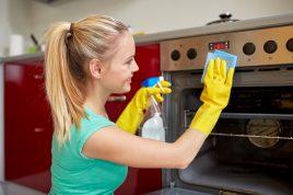 Menschen, Hausarbeit und Hauswirtschaft Konzept - glückliche Frau mit Flasche Spray Reinigungsmittel Reinigungsofen zu Hause Küche