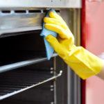 Nahaufnahme von Frau Hand in Schutzhandschuh mit Lappen Reinigungsofen zu Hause Küche